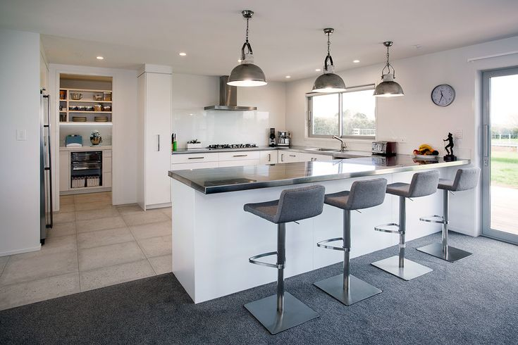 Stainless steel U-shaped kitchen benchtops, large walk-in scullery, white cabinetry, stainless steel pendant lights