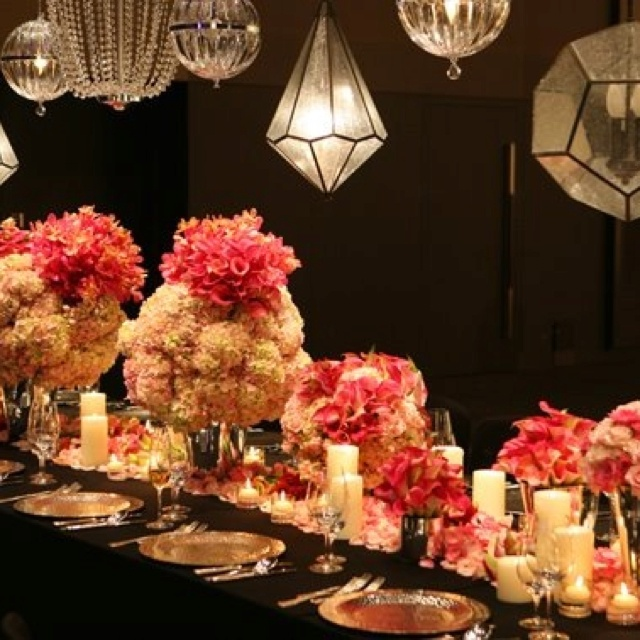 The contrast of vibrant flowers and metal chandeliers