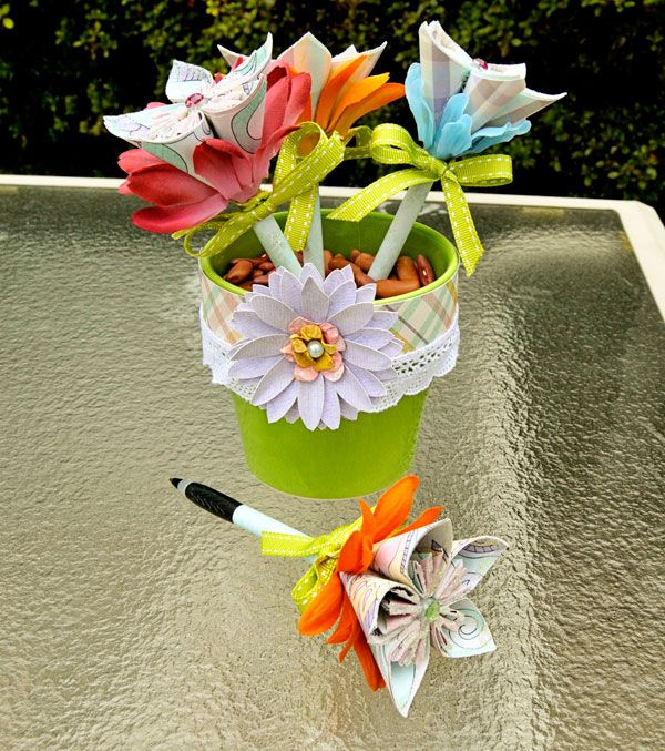 flowers on top of pens in a painted flower pot with beans inside.