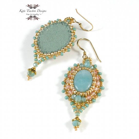 I created these lovely earrings using bead embroidery around soft green Amazonite ovals. Surrounding the focal beads are seed beads in shimmering metallic gold and pale pink quartz round beads. At the top and bottom of each earring are seafoam green Chinese crystals which I recently brought home from a trip to Shanghai. Hanging from the bottoms are more Chinese crystals topped with gold-plated bead caps. Around the edge of the earrings are seed beads in the same soft green. I backed the…