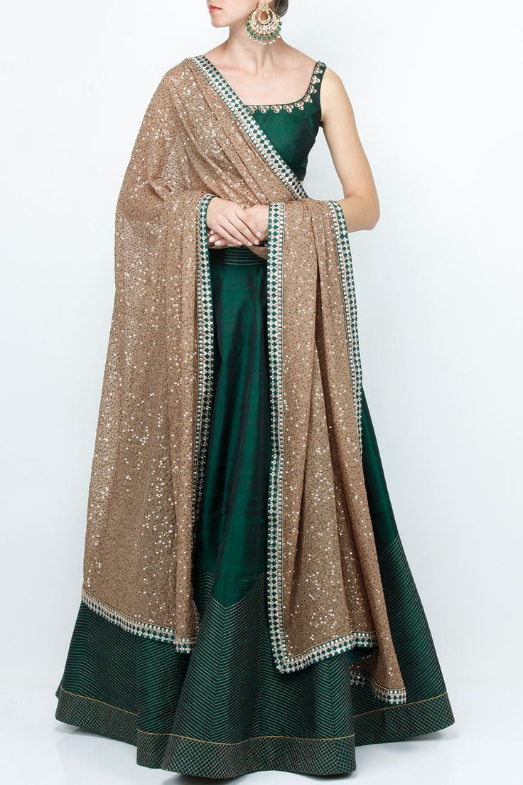Featuring a dark green raw silk lehenga with gold zari embroidered chevron border. It is paired with a matching choli with gold sequin hand work around neckline. It comes with a fawn dupatta with copper sequin work all over and dori embroidered border. Fabric: Lehenga & Blouse: Raw silk; Dupatta: Care Instructions: Steam press and dryclean only.
