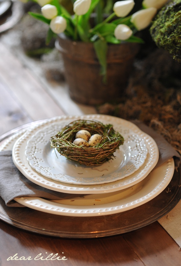 Simple & rustic Easter table decorated with tulips, moss, & a tiny bird's nest.