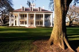 Southern plantation house complete with pillars and a wrap around porch.