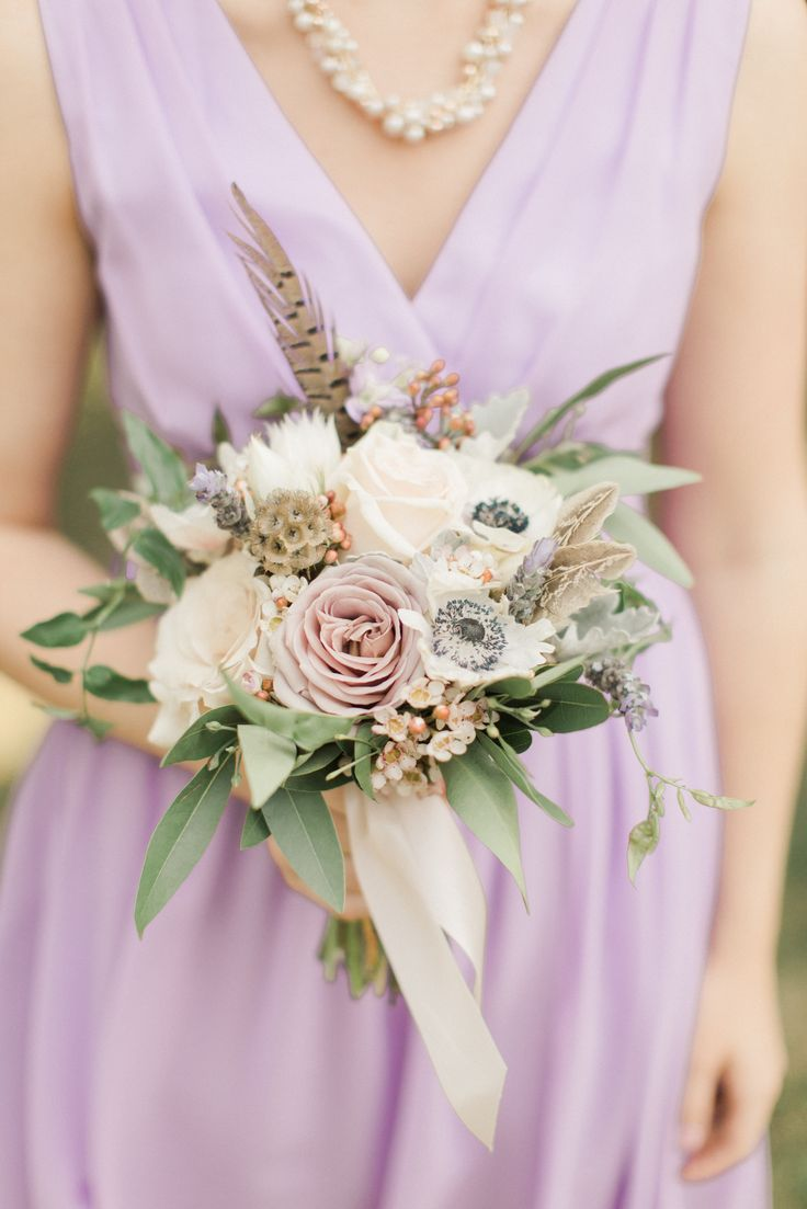 Blush roses and white anemones made up each bridesmaid bouquet, along with pheasant feathers for added texture.