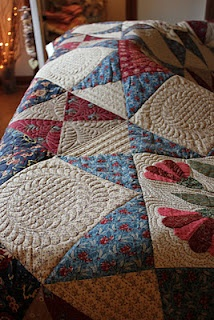 longarm quilted by the running chicken. Feathered circle.