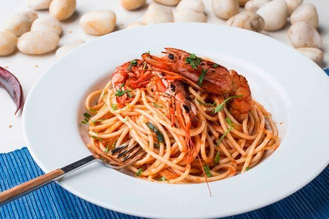 Spaguetti all'arrabiata con langostinos: Con nuestra salsa casera de tomate, albahaca y un ligero toque picante todo reforzado por un fumet de cabeza de gamba y rematado con langostinos a la parrilla.