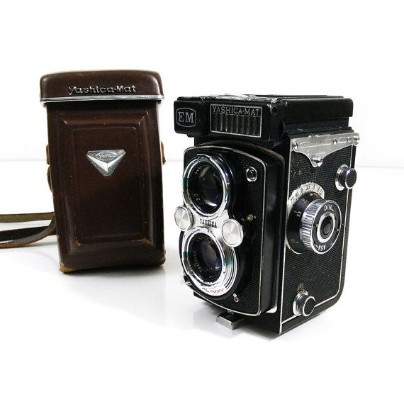 Yashica-Mat EM Camera  This vintage beauty is the Yashica-Mat EM twin lens reflex camera. The EM stands for exposure meter, which sets this camera apart from other models. Yashica-Mat EM Camera manual: http://www.butkus.org/chinon/yashica/yashica_mat-em/yashica_mat_em.pdf  This camera is being sold as is. It was purchased from a photographers estate and is untested. The plastic case around the exposure meter is cracked and loose, which is shown in the photographs. The camera is in otherwise…