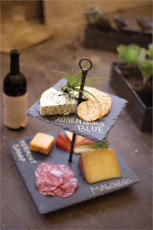 """This Two Tiered Slate Serving Stand is perfect for country farmhouse style entertaining. The rustic look and feel of slate gives the piece a natural elegance that fits right in to any style décor. The slate also acts as a chalkboard so you can identify your cheeses. Features a metal center rod with handle for easy transport. 12""""L x 12""""W x 14.5""""H Coordinates with our Glass Cloche and Slate Tray."""