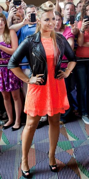 DEMI LOVATO    La otra jueza de The X Factor mostró su lado roquero al complementar un minivestido color naranja neón con una chaqueta en cuero estilo motociclista, ambos de Topshop. Unos zapatos peep toe de Christian Louboutin en charol negro y un elaborado peinado muy futurista completaron su look.