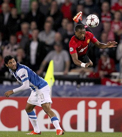 Manchester United's Patrice Evra takes to the air as Real Sociedad's Carlos Vela looks on
