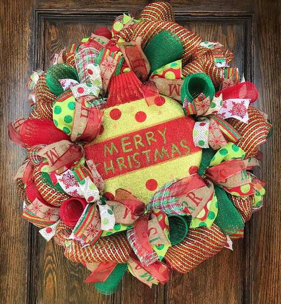 """Christmas wreath for front door 🎄🎅🏻❄️ This deluxe wreath is loaded with color! It is very full and measures 26"""" in diameter. The base is made out of a thick green and red foil along with green and red deco mesh and a red,green, and white basket weave mesh. There are 8 coordinating Christmas prints of ribbon throughout the whole design. The large Christmas ornament sign is the perfect centerpiece to complete the design. Just click & order and get it in plenty of time before the holiday..."""