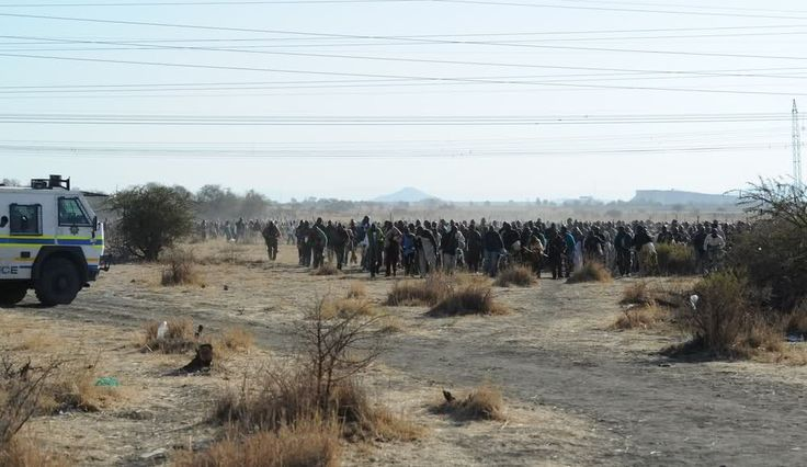 Marikana: A year on | A large group of miners faces police during clashes.