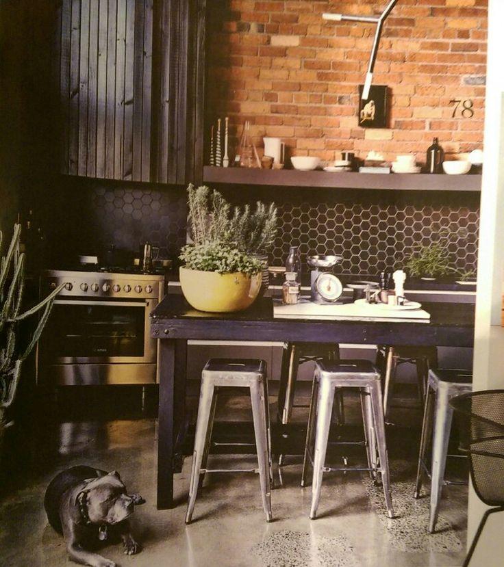 Chrome stools, black bench, black splashback, exposed brick wall