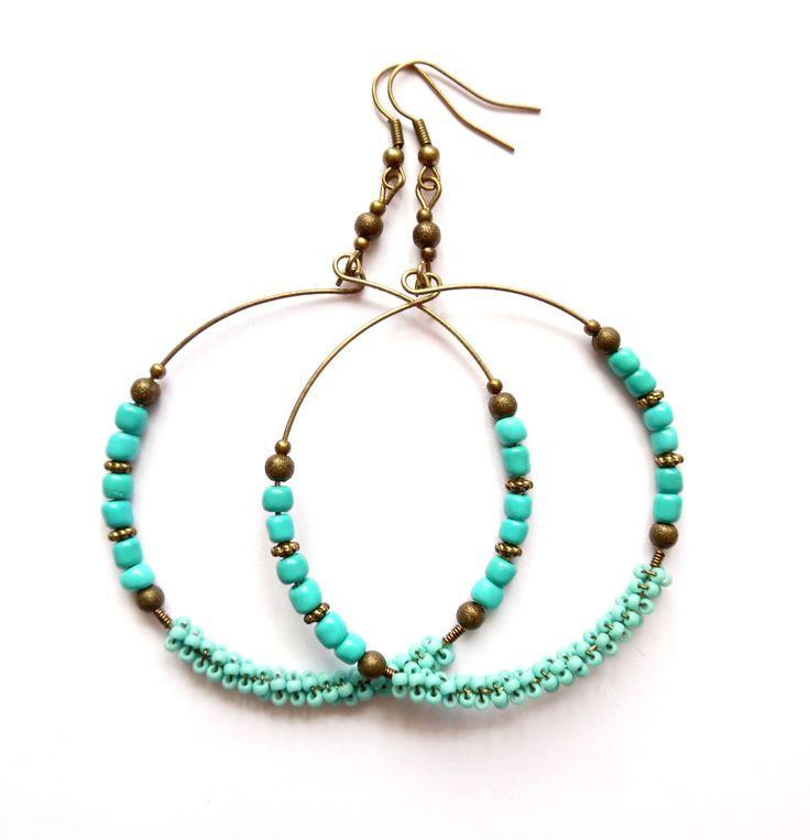 Örhängen med stora ringar i brons och turkos pärlor av glas.  Längd: 9cm