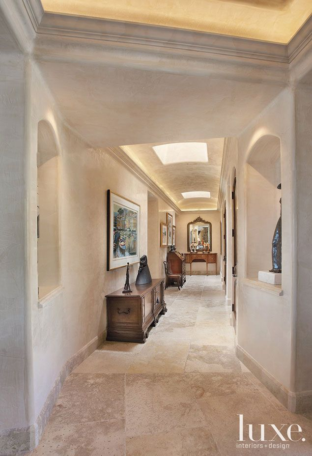 Throughout this home, walls and ceilings covered in Venetian plaster rarely present a right angle. The hallway's 17th-century chest, which sits under a serigraph by Howard Behrens, was found in Pienza, Italy. The 18th-century sideboard at the end of the hall was purchased in Bath, England.