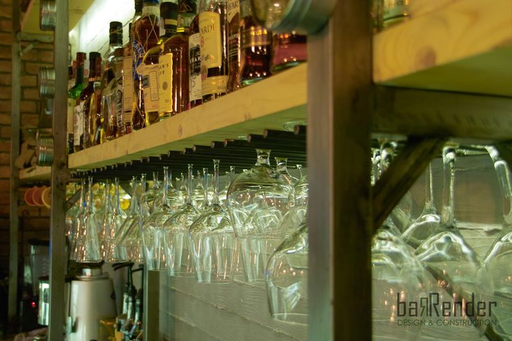 Glass rack made from naked iron rods and bottle shelves from naked formwork wood - Rag Doll Post modern bar in Athens.