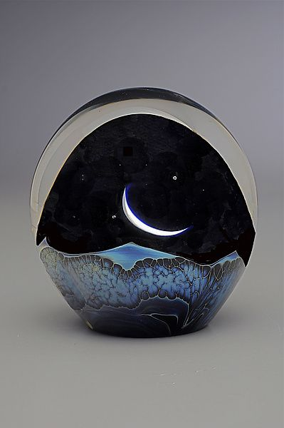 Moonrise Paperweight by Robert Burch - A crescent moon rises above a fantastical landscape created from multiple layers of blown glass. Encased in clear glass for depth and stability.
