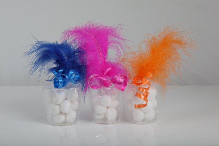 Shot glass, fun and funky wedding and party favours.  Complete with mint imperials or dolly mixtures for the sweet filling.  Styled with matching ribbon and feather.  Adds fun, style and colour to your celebration and a lovely token gift for your guests to enjoy.  Available in over 24 colours.  £1.99 each by www.fuschiadesigns.co.uk.