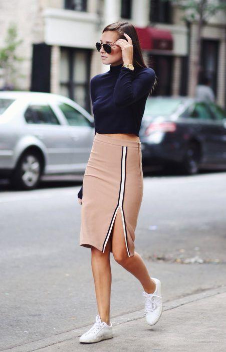 Chica usando una falda de lápiz, crop top en color azul y zapatillas en color…