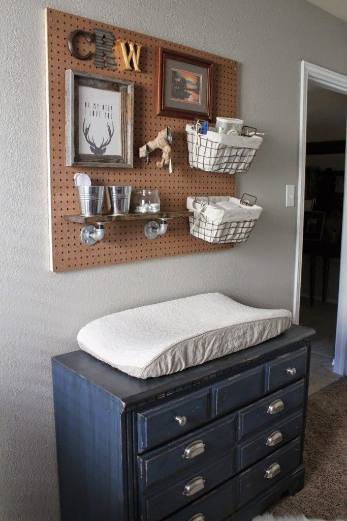 Love the use of a pegboard over the changing table to hold diaper supplies in this rustic hunting and fishing-themed nursery!