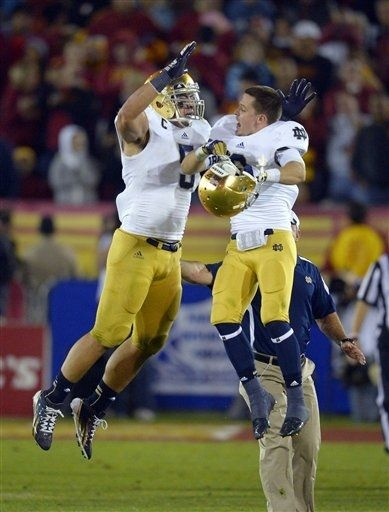 Notre Dame linebacker Manti Te'o, left, celebrates with wide receiver Robby Toma in the closing seconda of an NCAA college football game against Southern California, Saturday, Nov. 24, 2012, in Los Angeles. Notre Dame won 22-13. (AP Photo/Mark J. Terrill)