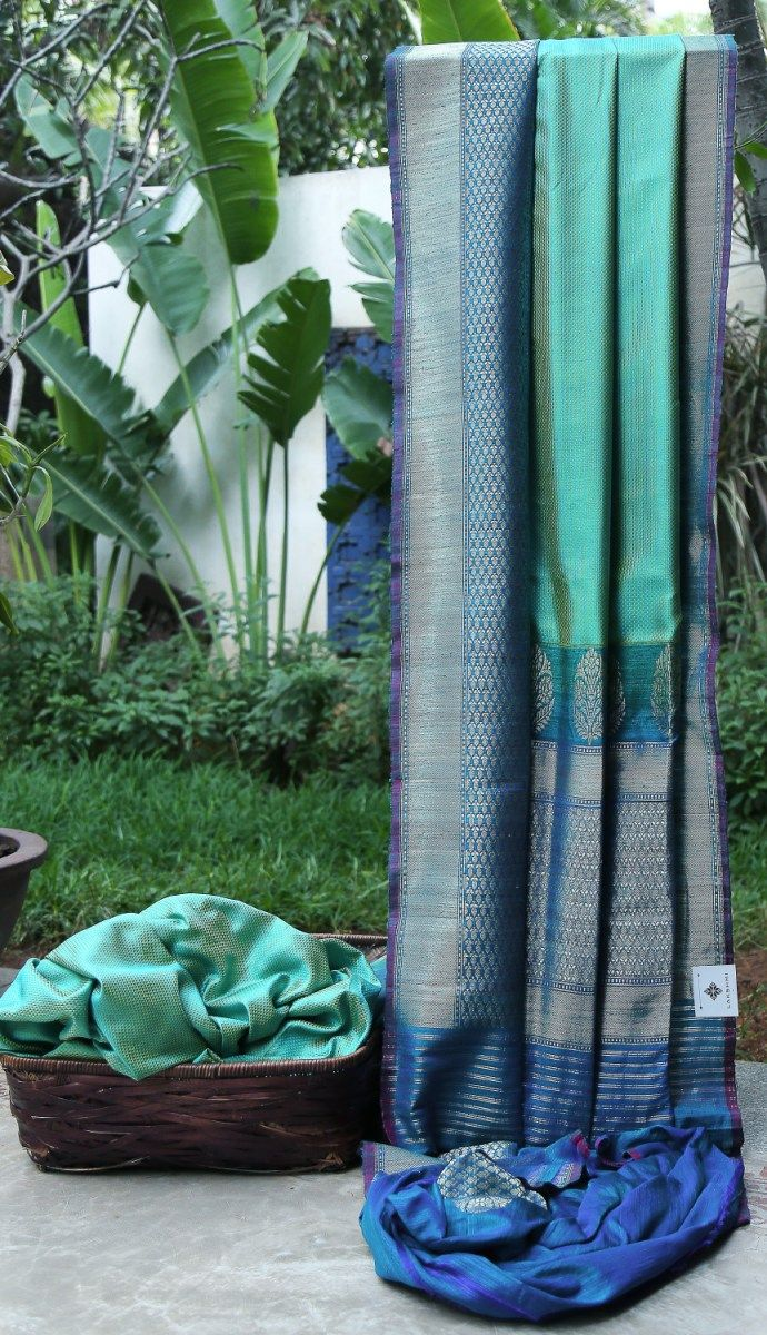 This iridescent light green and blue Benares silk has thread brocade in the base. The contrasting pallu and border are in lagoon blue with intricate weaving of gold zari giving this entire sari a s...