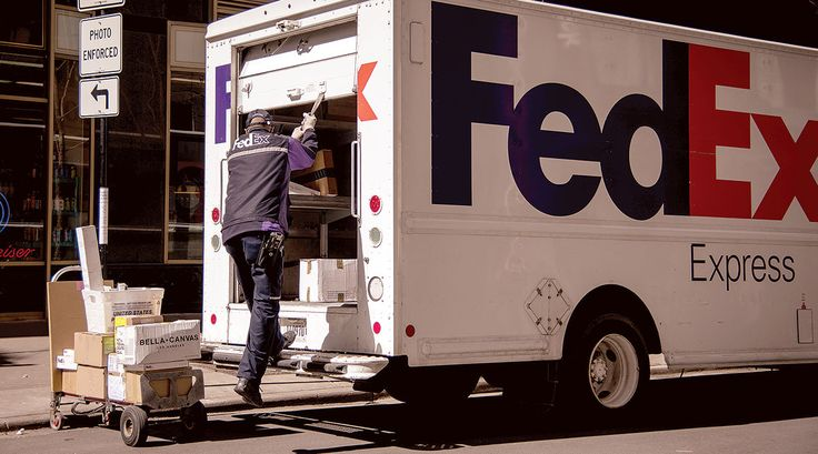FedEx Express employee loading parcels for delivery