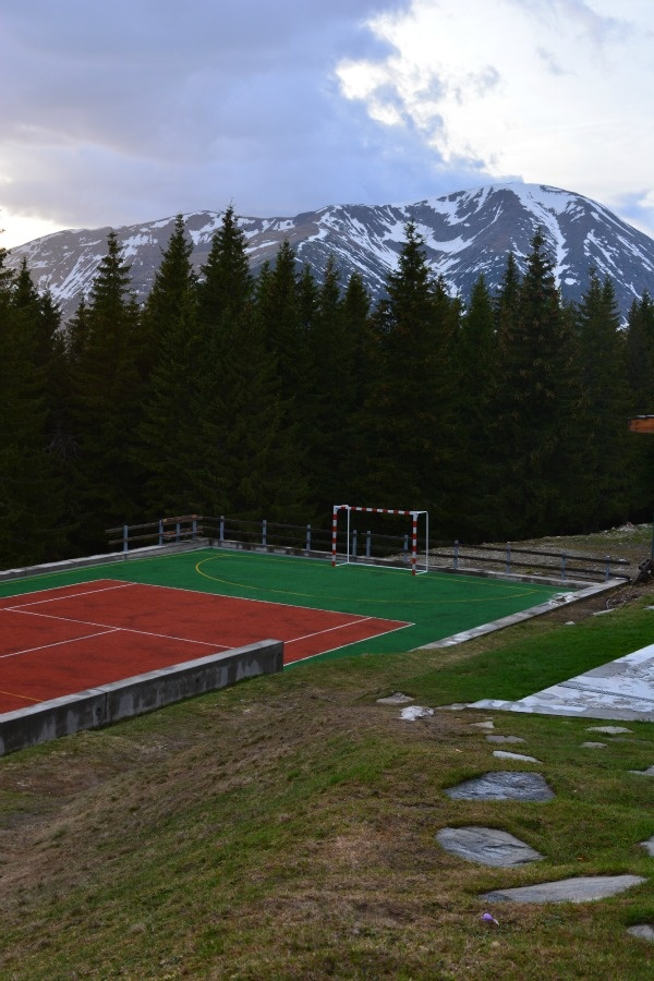 tennis court with mountains in the background