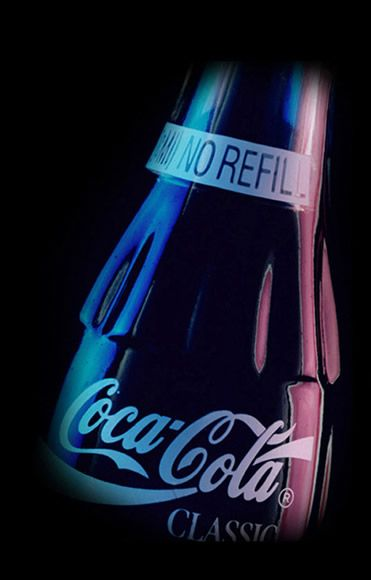 A Classic Coca Cola bottle in a dark setting, with dim blue and red lights reflecting off of it.