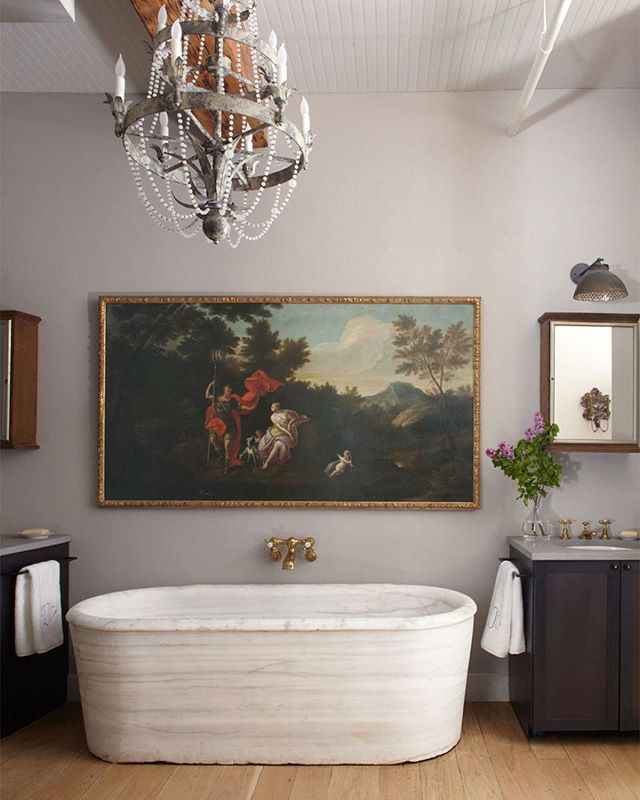 We don't know which we love more: the marble tub, antique painting, or amazing chandelier.