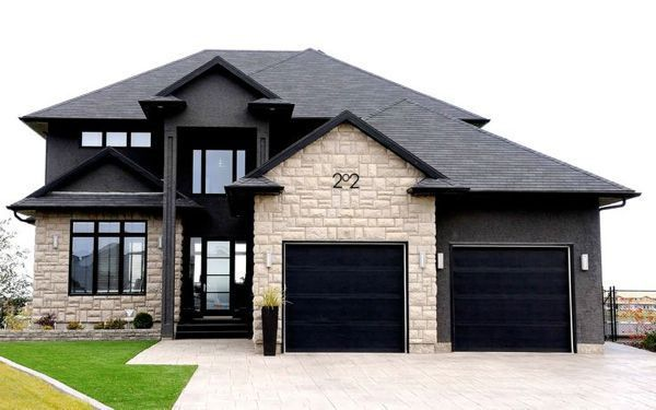 home with black windows, charcoal roof and siding with off white brick/stone.