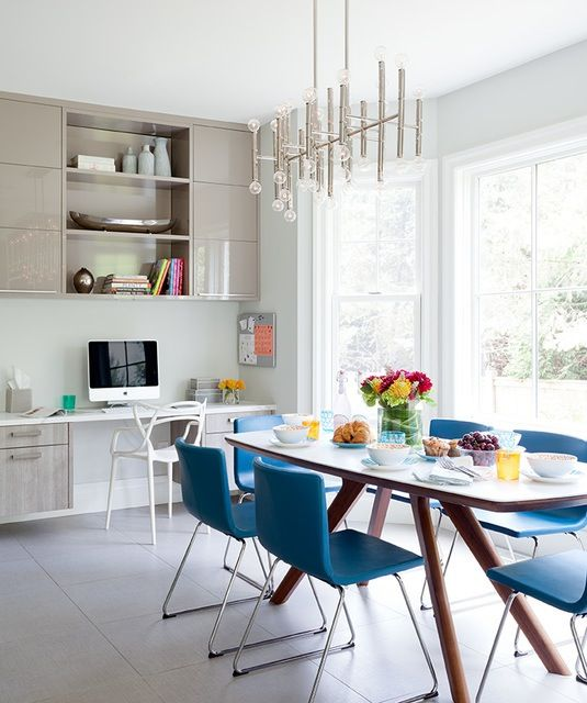In the dining area, bright peacock blue chairs are unexpected and playful against the clean look of the kitchen.A small desk area close to the breakfast nook keeps the busy family organized.