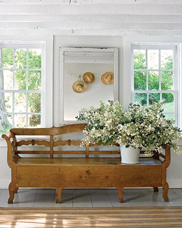 The Hall  Swedish antiques abound, including a large bench that holds bedding and table linens underneath the seat and an oversize white mirror reflecting a collection of well-worn gardening hats