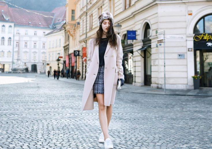 Fashion Blogger Veronika Lipar of Brunette from Wall Street wearing white sneakers from Diesel, black and white plaid tweed mini skirt from Storets, black silk blouse from Juicy Couture, off-white double breasted wool coat from MaxMara, faux fur headband, chain strap shoulder white bag, blue leather gloves on the street in Ljubljana in winter