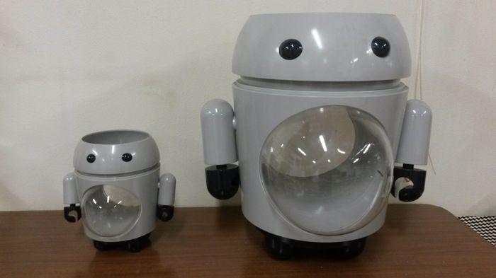 2 vintage opslag robot in kunststof. Deze robot zijn zeer praktisch. Het is mogelijk om items te slaan op de robot hoofd of binnen hun buik, die wordt geopend als een venster. De items inschakelen een 360 graden uitzicht van de items binnen, alsof ze twee kleine vitrines. De armen en handen zijn afneembaar. Ik weet niet de ontwerper, maar het artikel is heel schattig.  Afmetingen: ca. 47 x 42 cm en 24 x 21 cm.