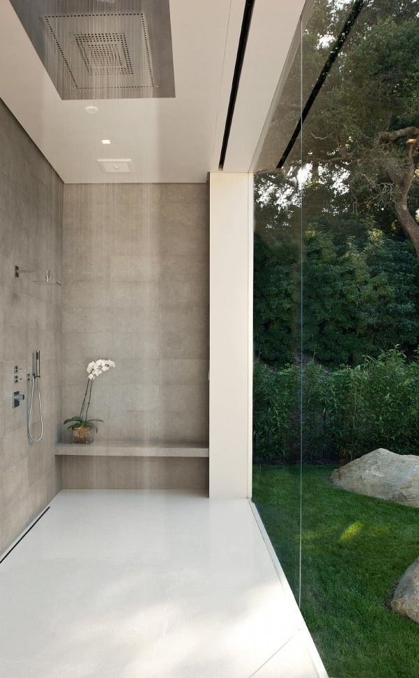 Love the sleek bathroom in this minimalist home. The rains shower and linear drain system add to the look