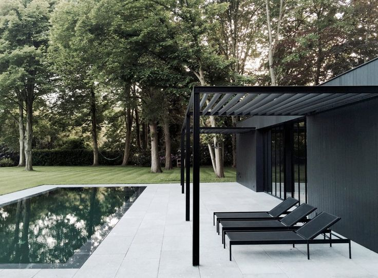 Pool patio with black steel pergolas, in front of a black box-shaped house. Project CD Poolhouse …