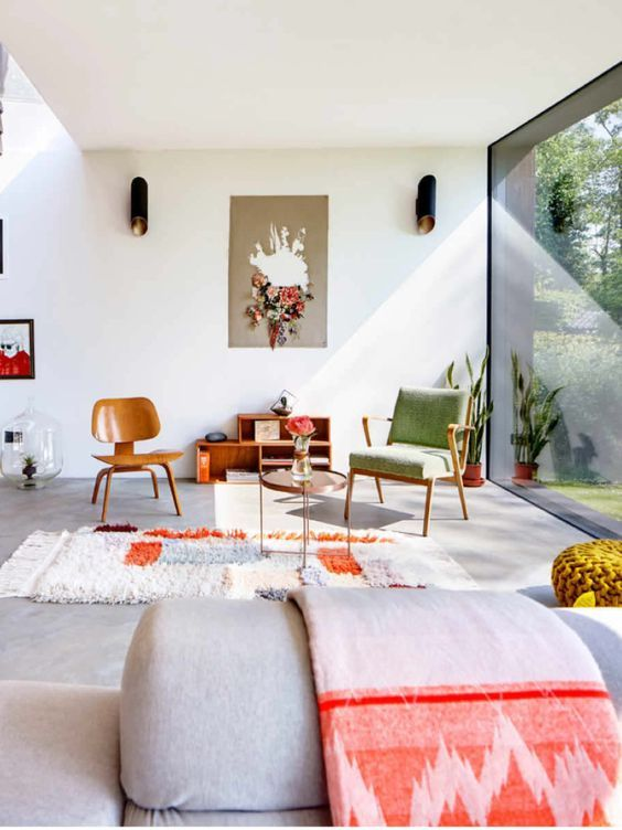 Das perfekte Wohnzimmer! Würdet hier euch nicht auch gerne auf die Couch fläzen? Hier harmoniert einfach alles. Die Vintage-Stühle und der Vintage-Teppich kombinieren bestens mit dem grauen Steinboden und der grauen Couch. Und dann auch noch dieses Licht! Traumhaft schön.