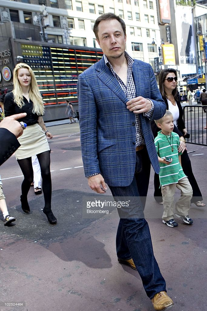 Elon Musk, chairman and chief executive officer of Tesla Motors, walks outside the Nasdaq Marketsite followed by fiancee Talulah Riley, left, in…