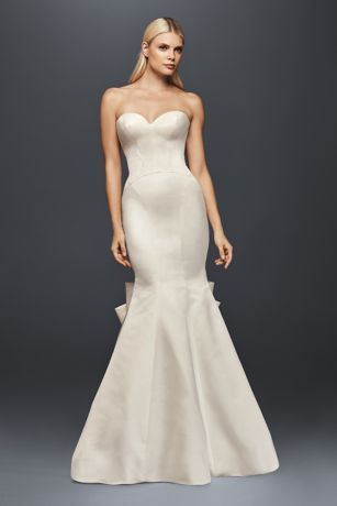 This duchesse satin mermaid gown perfectly captures the allure of Old Hollywood glamour. The sleek, seamed silhouette gorgeously plays up your curves while the back has a few stunning details: buttons trail from the bodice, and a grand bow flourishes atop the tulle train.   Truly Zac Posen, a David's Bridal exclusive  Polyester  Sweep train  Back zipper; fully lined  Dry clean  Imported