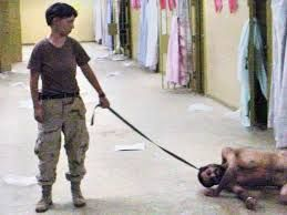 US soldier, Lynndie England posing with a detainee on a leash.