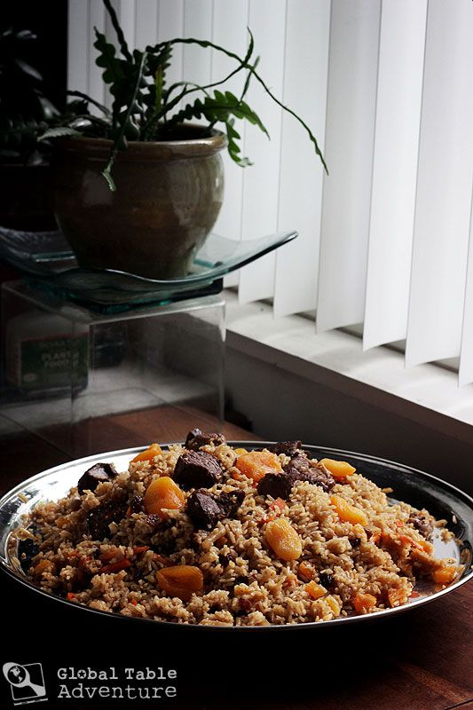 "Lamb Plov with Dried Apricots, a traditional recipe from Tajikistan made with rice, carrot, turnip, onion, cumin, and lamb. (Recipe includes ""Top 5 Tips for eating from a Communal Platter"")"