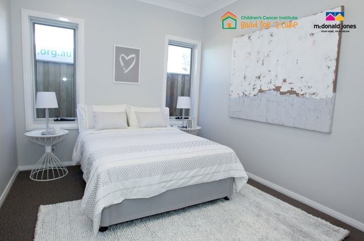 A Bedroom in the #BuildforaCure home furnished by Freedom and built by #McDonaldJonesHomes. #whitedecor #decorating #interiordesign #bedroom #bedroomideas #rug #lamps #art #linen #charity