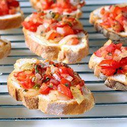 Snij het stokbrood in reepjes van ongeveer 1,5cm. Rooster de sneetjes aan beiden kanten op de bbq. Smeer de broodjes aan één kant in met olijfolie. Hak de knoflook fijn en verdeel deze over de broodjes. Snijd de tomaten en ui in kleine blokjes, beleg de broodjes en voeg tot slot wat fijngehakte basilicum toe. Naar smaak peper en zout toevoegen.