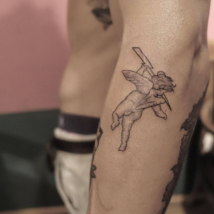 Cherub tattoo on the left forearm.