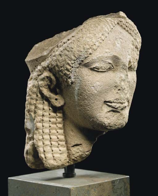 Greek Kore, Greek limestone head of a Kore, Archaic period, late 6th century B.C. Greek Kore, finely modelled, her face with archaic smile, her hair worn in wavy tresses parted above her high forehead and framing her face in triangular formation, tresses drawn back over the crown of the head, behind the ears and falling down over the back of her neck, diadem with two long strands lying over her tresses, bearing traces of reddish pigment, pierced earlobes, 17.8 cm high. Private collection