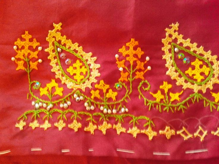 Yellow mango motiff kutch/sindhi stitch with orange and green detailing. Embellished with tiny pearls & sequins. Embroidered on a silk deep red blouse piece.
