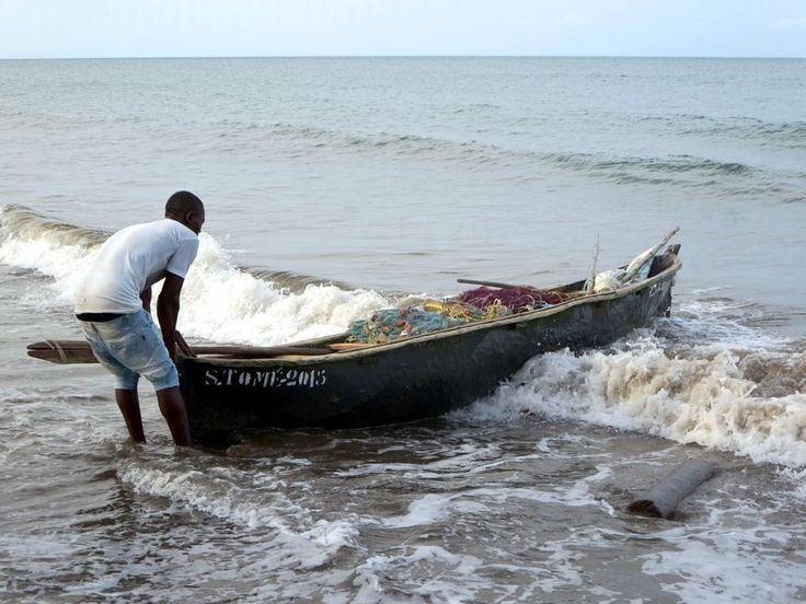 A fisherman pulls in his canoe at Praia Melão on Sao Tome Island, São Tomé and Príncipe.