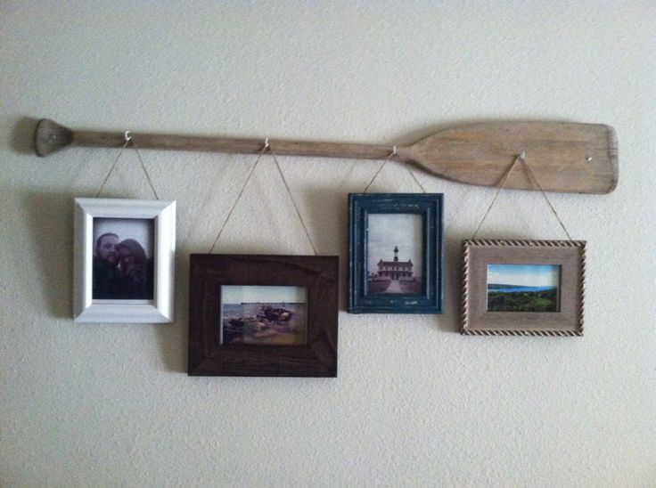 Rustic oar picture hanger... Old worn out wooden oar with hooks and rustic picture frames. Colors textures work well with rustic or nautical decor! Still trying to figure out if I want to paint or stain the oar, or keep it natural?