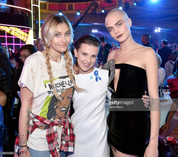 (L-R) Paris Jackson (age 19), actress Millie Bobby Brown (age 13), and actress-model Cara Delevingne (age 24) attend the 2017 MTV Movie And TV Awards at The Shrine Auditorium on May 7, 2017 in Los Angeles, California.